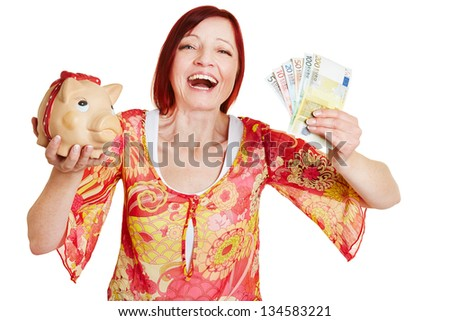 Successful woman cheering with piggy bank and Euro money bills - stock photo