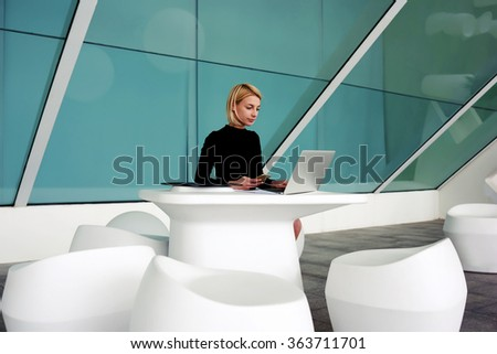 Successful woman entrepreneur waiting for a call on mobile phone while sitting with open net-book in office interior, female economist holding cell telephone in hand during work on laptop computer - stock photo