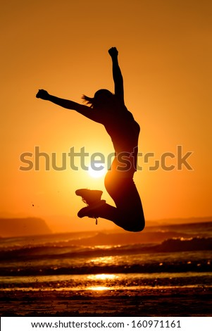 Successful woman jumping, dancing and having fun on sunset in beach. Freedom and happiness concept. Girl celebrating work out success. - stock photo