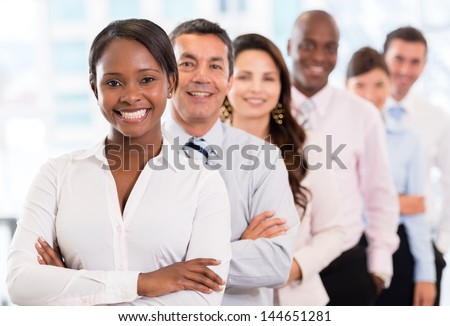 Successful woman leading a business group and looking happy - stock photo