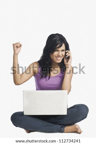 Successful woman talking on a mobile phone and clenching fist - stock photo