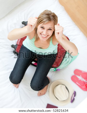Successful woman trying to close her suitcase on her bed - stock photo