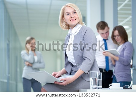 Successful woman with digital tablet and colleagues in the background - stock photo