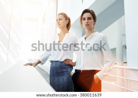 Successful women entrepreneurs with serious look posing while standing in modern office interior, team of skilled female partners in formal wear resting in hallway after meeting with important clients