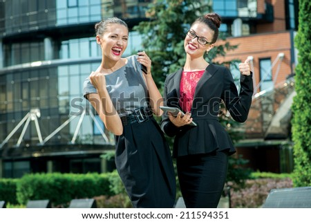 Successful women. Two young businesswoman talking on the street and enjoyed their success while standing in front of an office building in the park - stock photo