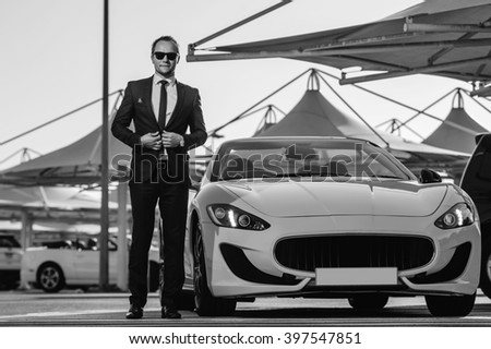 Successful yang businessman stands next to yellow cabrio car.