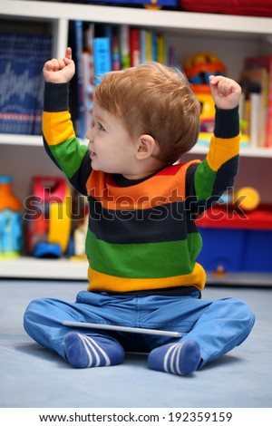 Successful 2 years old boy winning using a digital tablet computer - stock photo
