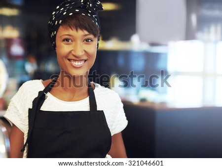 Successful young African American business owner standing in her coffee shop in an apron and bandanna smiling at the camera - stock photo