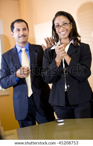 Successful young African-American female office worker getting pat on back from middle-aged Hispanic male manager - stock photo