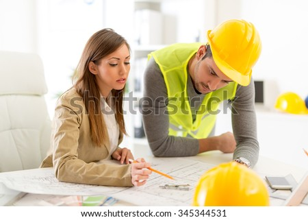 Successful young architects discussing construction plans in office. - stock photo