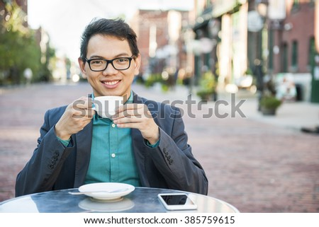 Successful young asian man sitting and smiling in relaxing outdoor cafe with mobile phone holding cup of coffee enjoying his break - stock photo