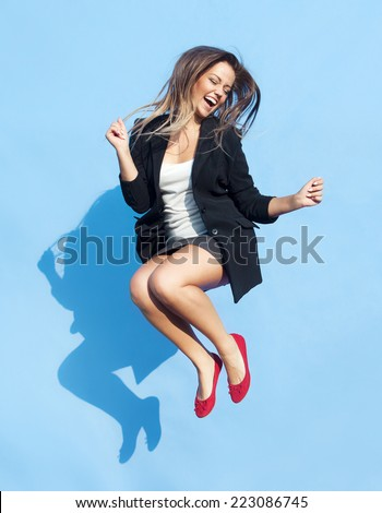 Successful young attractive laughing woman jumping up - stock photo