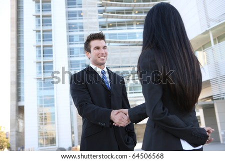 Successful young business man and woman shaking hands at office building - stock photo