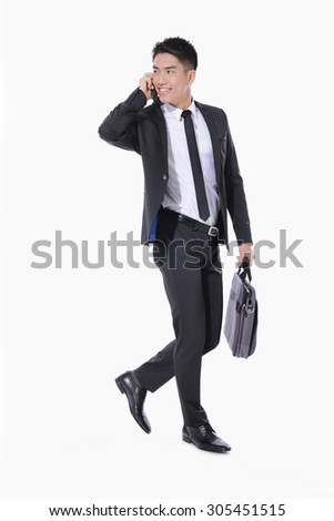 successful young business man walking carrying a suitcase , speaking on cellphone  - stock photo