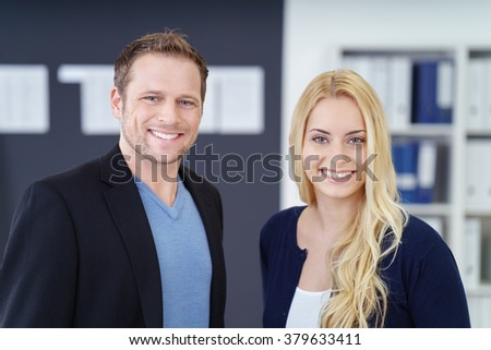 Successful young business management team of an attractive man and woman posing together in the office smiling at the camera - stock photo