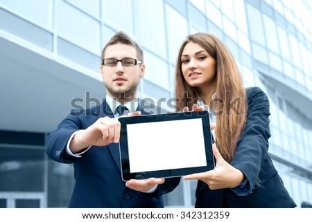 Successful young business people are holding a tablet, standing in front of his office. - stock photo