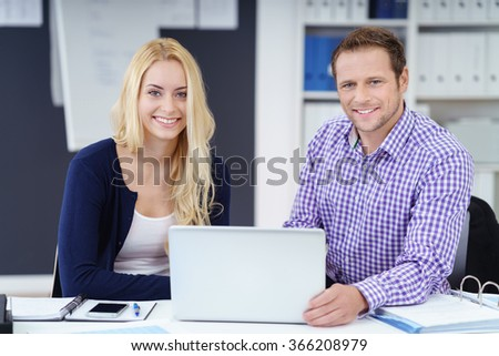 Successful young business team, a man and woman, sitting at a desk in the office working on a laptop computer smiling at the camera - stock photo