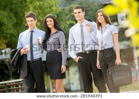 Successful young business team during a coffee break, walking on a park and enjoying a sunny day. - stock photo