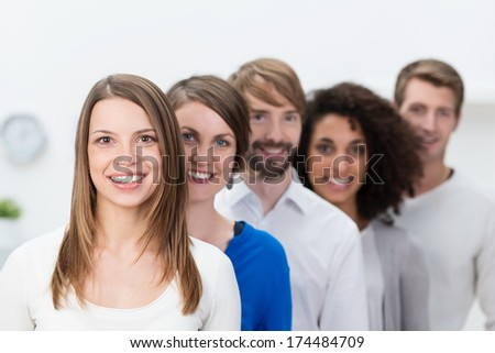 Successful young business team posing in an oblique line behind their beautiful young female team leader - stock photo