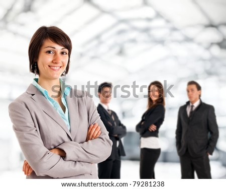 Successful young business woman. Businesspeople in the background. - stock photo