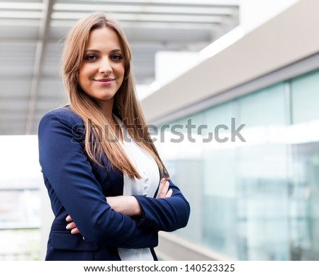 Successful young business woman looking confident and smiling - stock photo