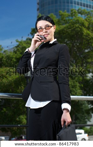 Successful young business woman talking cellphone. Outdoor. - stock photo