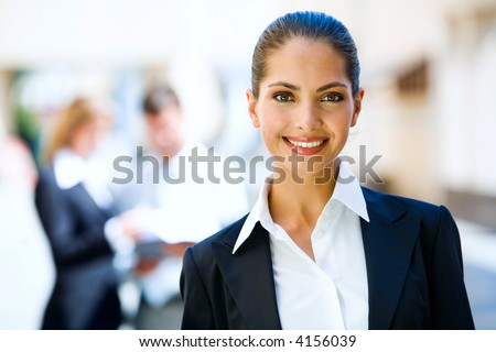 Successful young business woman with charming confident smile - stock photo