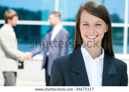 Successful young business woman with charming smile - stock photo