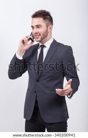 successful young businessman in classical stylish suit talking on the phone on a white background gesturing hands. - stock photo