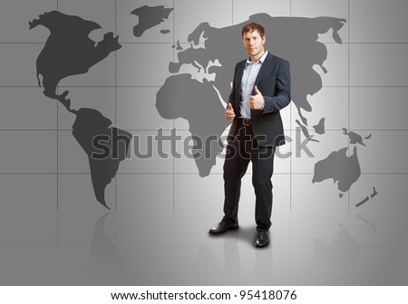 Successful young businessman in front of world map with thumbs up - success or achievement concept - stock photo