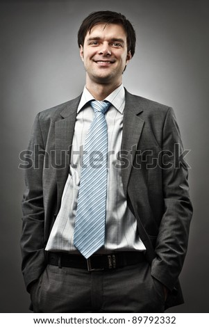 Successful young businessman on gray background - stock photo