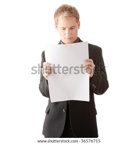 Successful young businessman reading blank card (newspaper) in studio - stock photo
