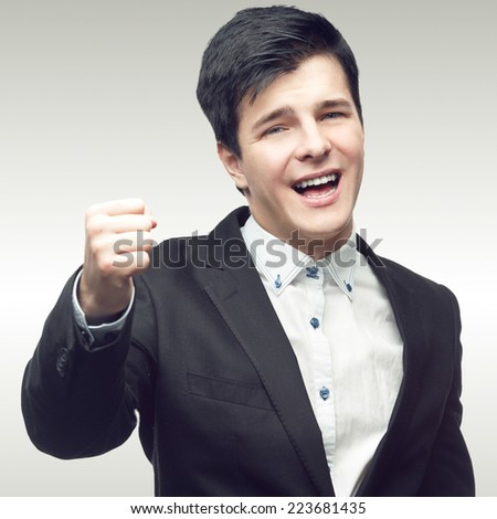 successful young businessman standing over gray background