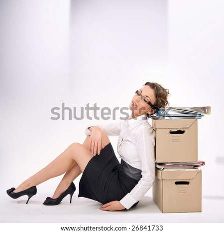 Successful young businesswoman next to pile of documents, lots of copy space - stock photo