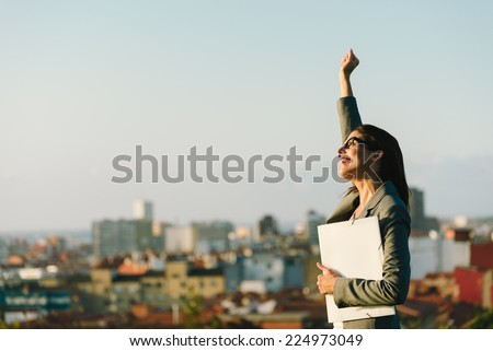 Successful young businesswoman raising arm celebrating business  or job achievement towards city background. Professional happy woman walking outside. - stock photo
