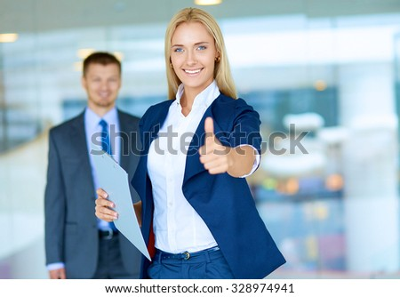 Successful young businesswoman showing ok - stock photo
