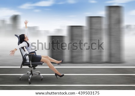 Successful young businesswoman sitting on the chair with growth graph and city background - stock photo