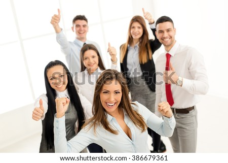 Successful young businesswoman standing proudly with her young business team. They showing thumbs up and looking at camera. - stock photo