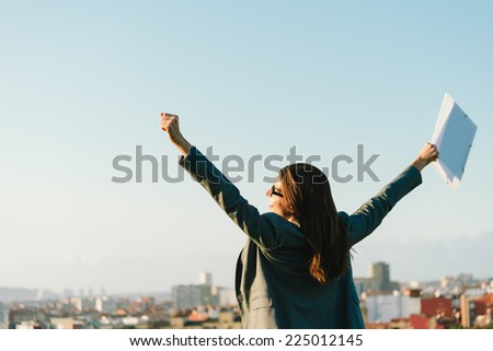 Successful young businesswoman with arms up celebrating business  or job success towards city skyline. Professional happy woman outside. - stock photo