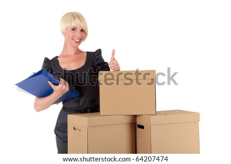 Successful young businesswoman with thumb up and holding a folder behind a stack of postal boxes. Studio shot. White background