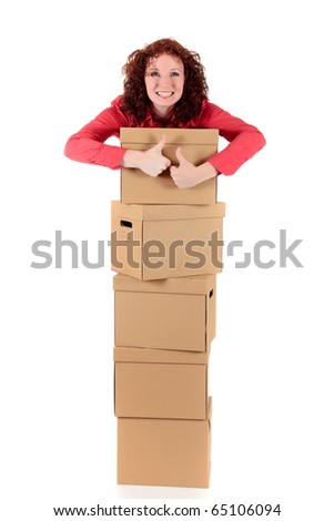 Successful young businesswoman with thumbs up standing behind a stack of storage boxes. Studio shot. White background