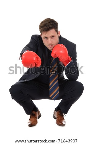 Successful young caucasian businessman with boxing gloves squatting. Right hand punch. Studio shot. White background. - stock photo