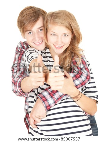 successful young couple hugging and thumbs up, white background - stock photo