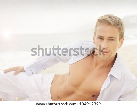 Successful young good-looking guy on the beach with relaxed open shirt - stock photo