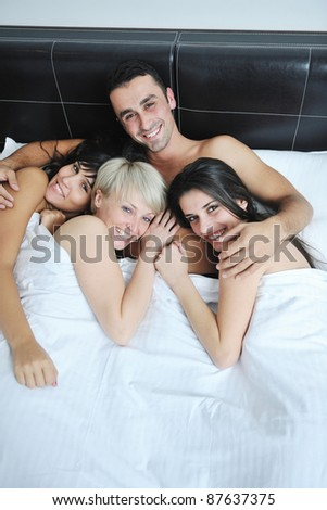 successful Young handsome man lying in bed with three sleeping girls - stock photo