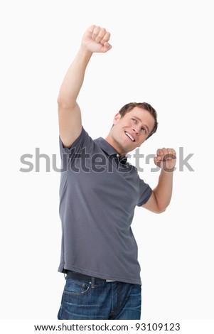 Successful young man celebrating against a white background - stock photo