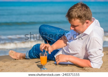 successful young man resting by the sea with cocktail - stock photo