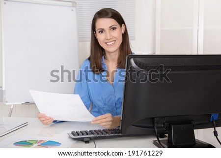Successful young smiling business woman sitting in her office. - stock photo