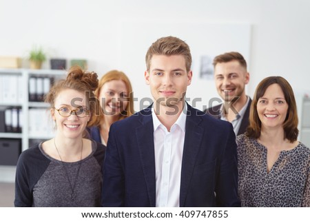 Successful young team leader with his business team of diverse men and women standing in the foreground smiling at the camera - stock photo