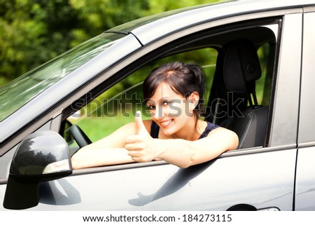 successful young woman in the car with thumb up